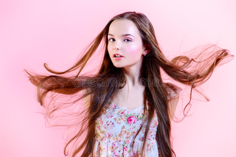 Windy hairs. Elegant girl with natural make-up and beautiful long hair in motion posing over pink background. Fashion. Hairs stock photography