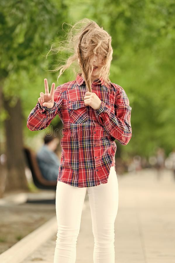 It is windy outside. Little child with messy hair on summer day. Cute kid enjoy her hair waving and showing victory royalty free stock photography