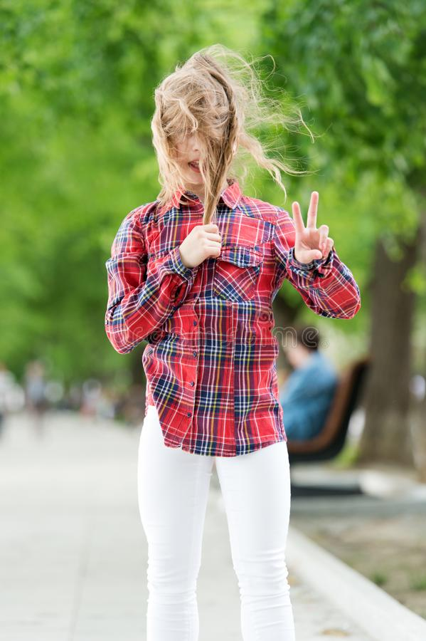 It is windy outside. Little child with messy hair on summer day. Cute kid enjoy her hair waving and showing victory royalty free stock photos