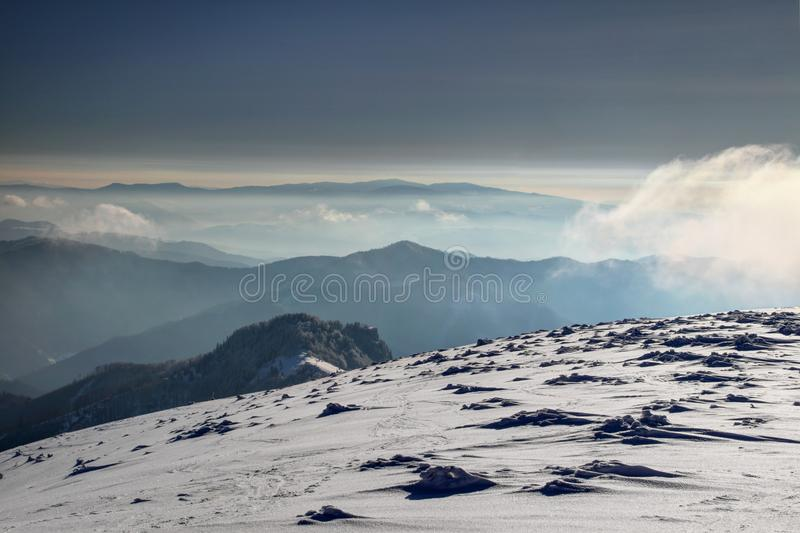 Windy snowfield and hazy mountain silhouettes in Fatra Slovakia royalty free stock photos