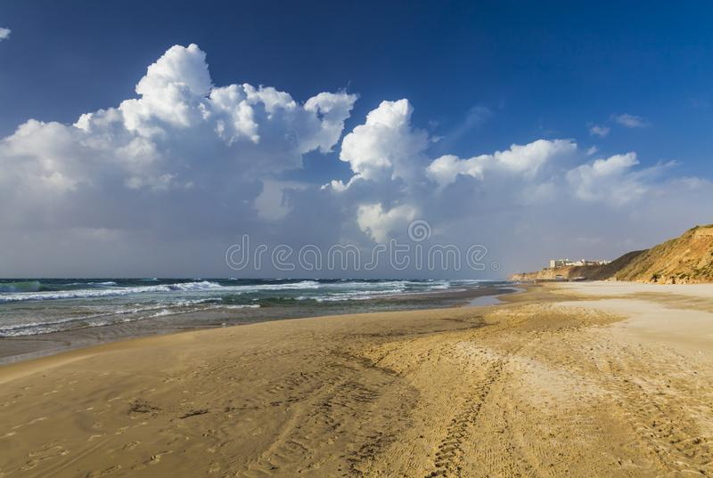 Windy sunny day on the beach. Stormy sea, strong wind, white foam on the waves. Netanya, Israel, Mediterranean sea. Overcast. Cloudy sky. Swimming is prohibited royalty free stock photo