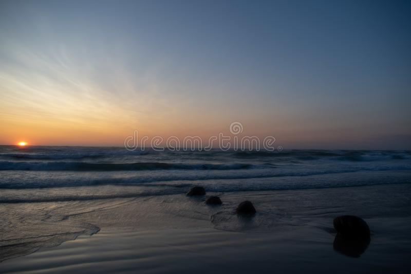 Windy Sunset at the beach. Løkken Denmark. Colorful and moody light from the sun. Waves from  the ocean stock photo