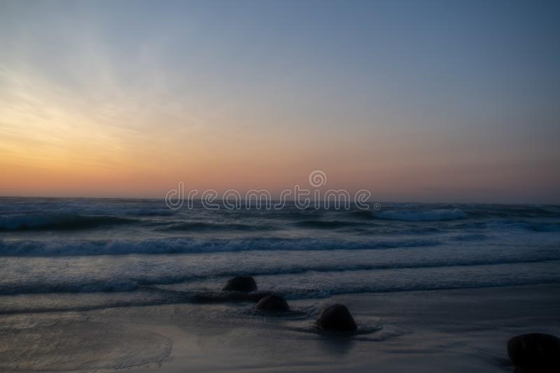 Windy Sunset at the beach. Løkken Denmark. Colorful and moody light from the sun. Waves from  the ocean stock images