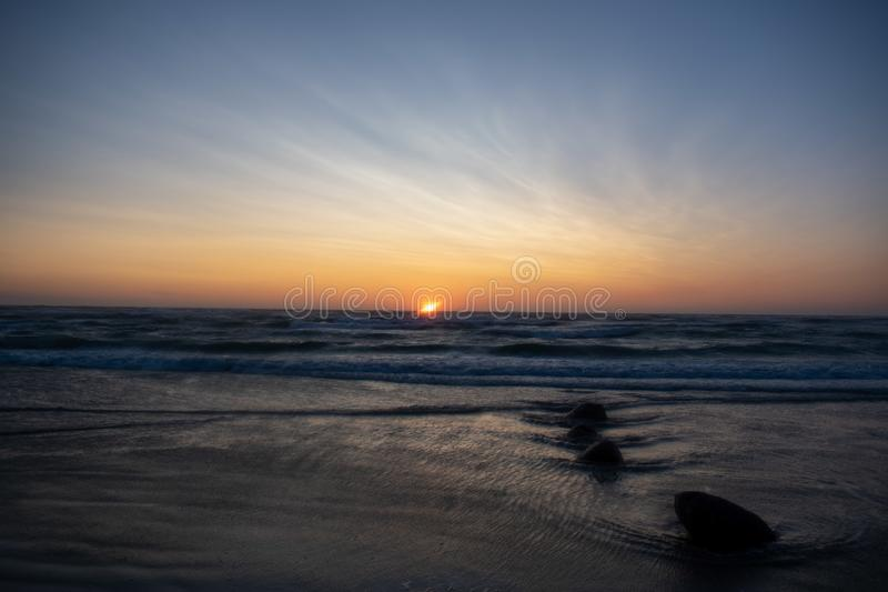 Windy Sunset at the beach. Løkken Denmark. Colorful and moody light from the sun. Waves from  the ocean royalty free stock photo