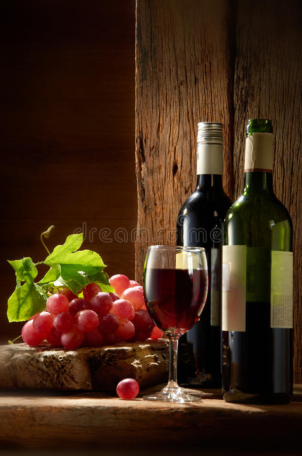 Wine. Still-life with two wine bottles and glass over wooden textured background