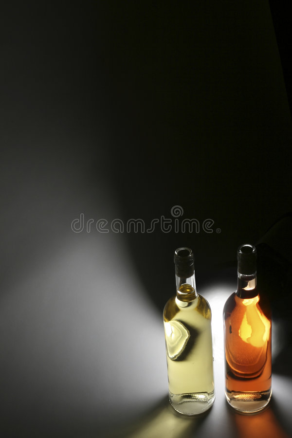 Wine. Two bottles of wine, rose and white wine in front of a light source with lots of copy space royalty free stock photo