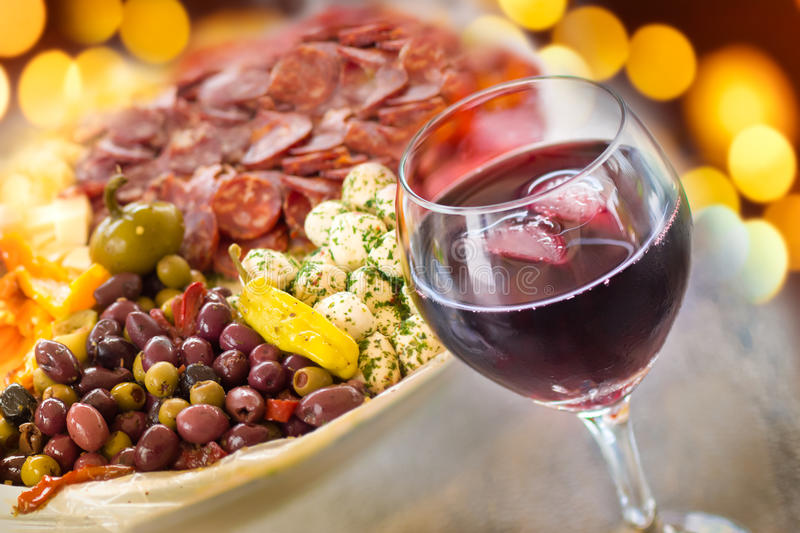Wine and Antipasto. A glass of red wine with a platter of Italian antipasto and festive lights behind stock photo