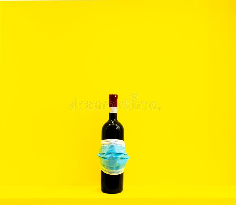 Wine background. Bottle of wine with label covered with face mask in yellow background. Blank space design background royalty free stock photos