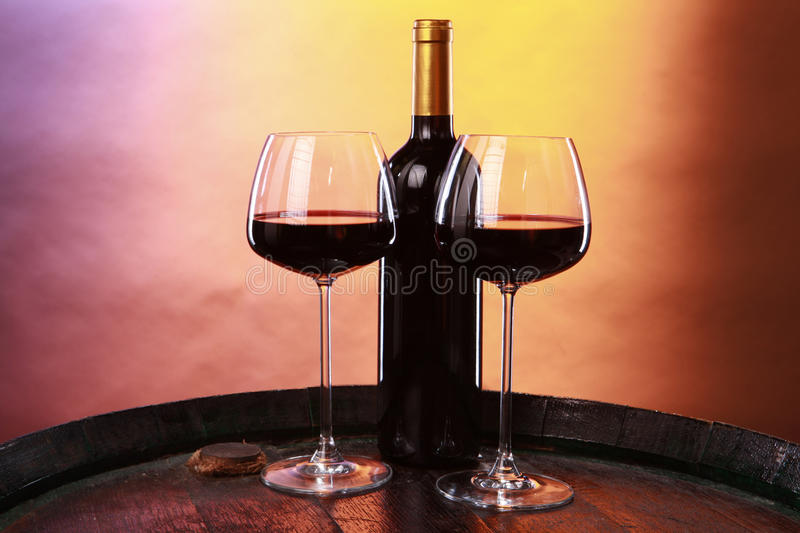 Wine on a barrel. A couple of elegant glasses of red wine on an old barrel top stock photos