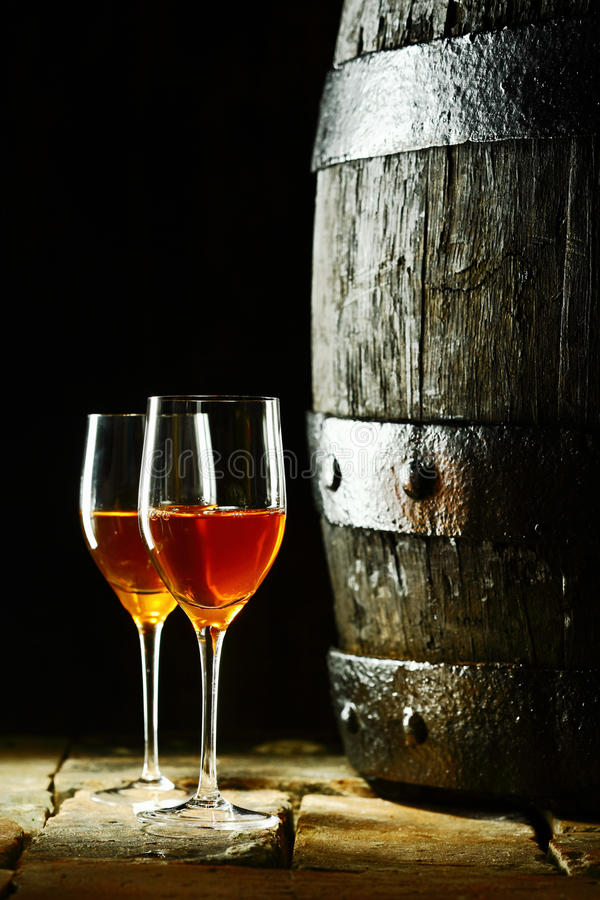 Wine barrel with glasses of sherry. Old oak wine barrel with two glasses of sherry against a dark background reminiscent of a cellar in a winery royalty free stock photos