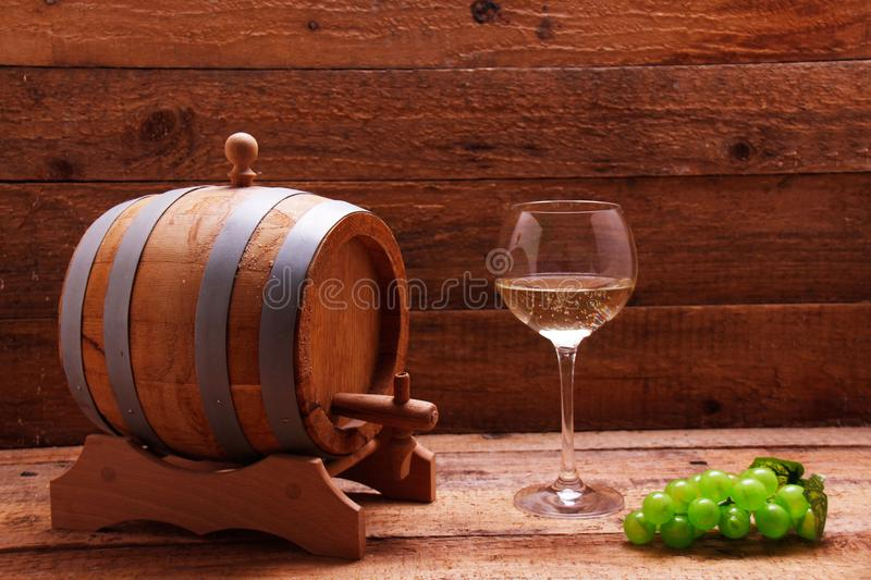 Wine barrel, wine grapes and a glass of wine royalty free stock photo
