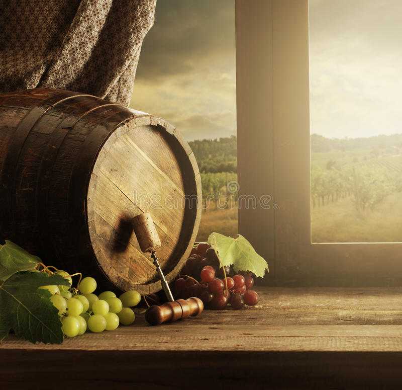 Wine barrel. And grapes with vineyard on background stock images