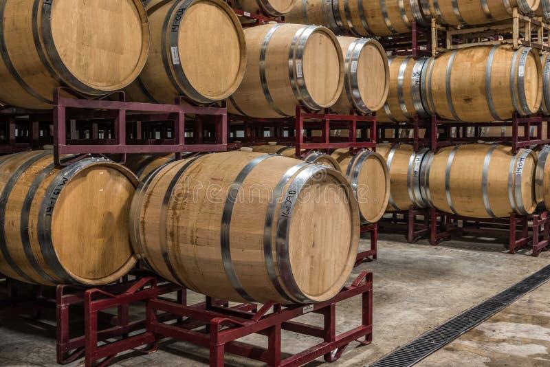 Wine Barrel Inventory on Racks. Vineyards inventory of wine barrels stacked on red metal racks stock photo