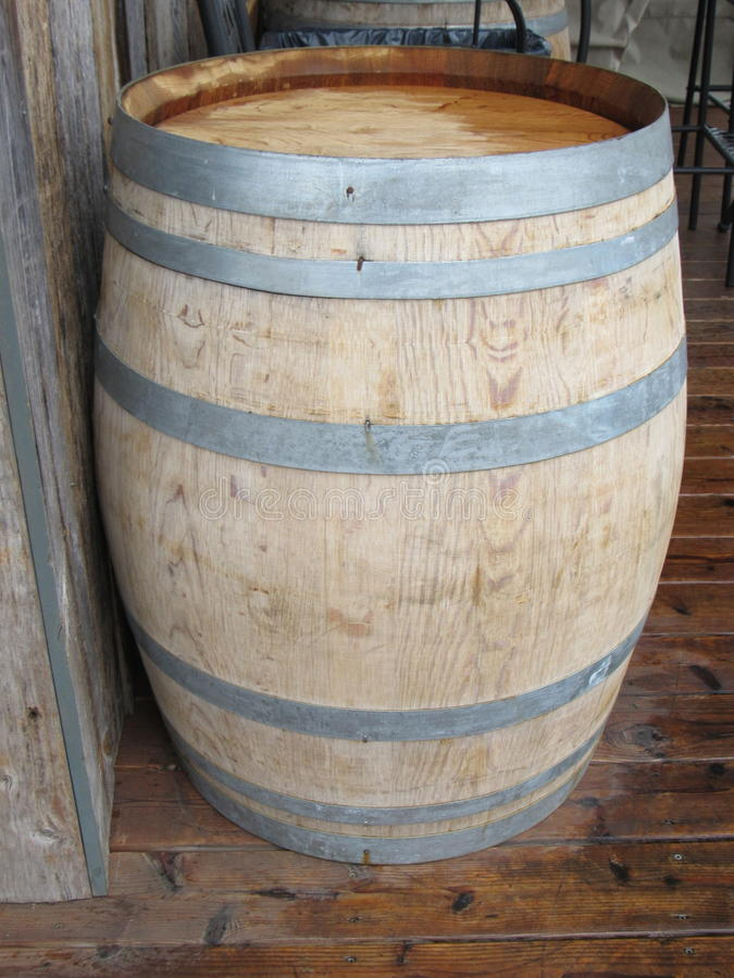 Wine barrel. Oak wine barrel on pock- marked wooden porch floor, leaning against rough wood wall royalty free stock photo