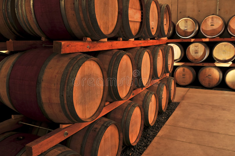 Wine barrels. Stacked oak wine barrels in winery cellar royalty free stock photo