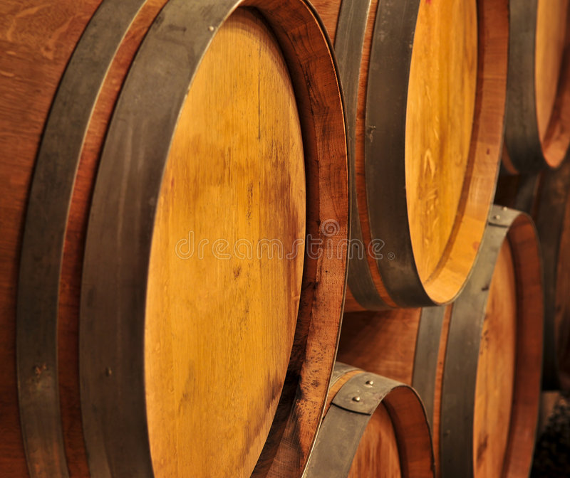 Wine barrels. Stacked oak wine barrels in winery cellar stock image