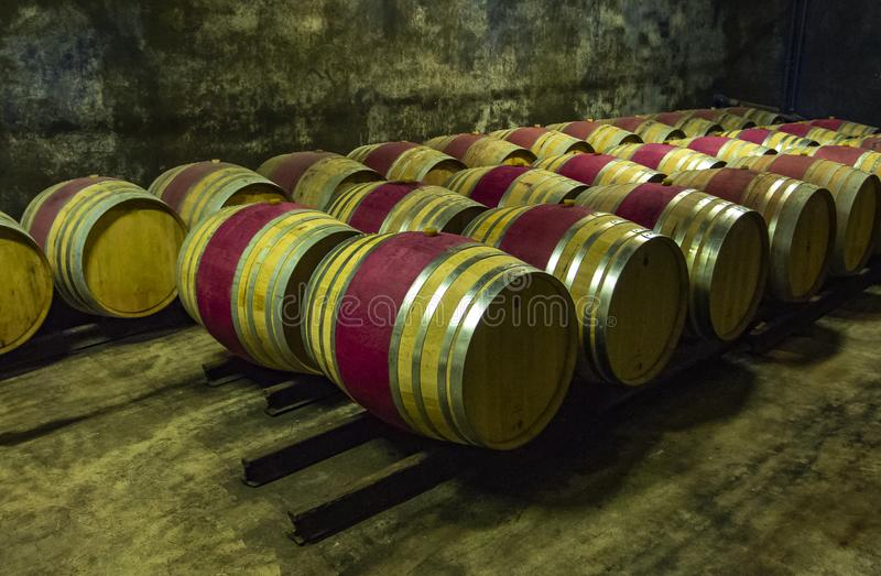 Wooden wine barrels in a basement. Wine barrels in the antique cellar. Cavernous wine cellar with stacked oak barrels for maturing red wine stock photos