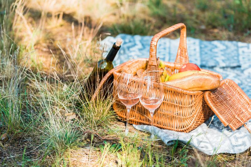 Wine bottle basket with loaves on grass. At picnic stock images
