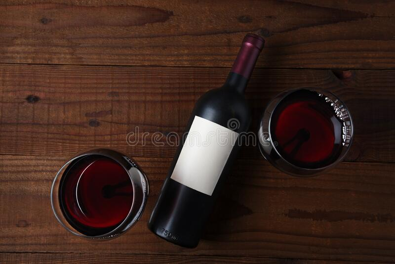 Wine Bottle with a blank label laying on its side and two full wine glasses on rustic wood table . stock photography