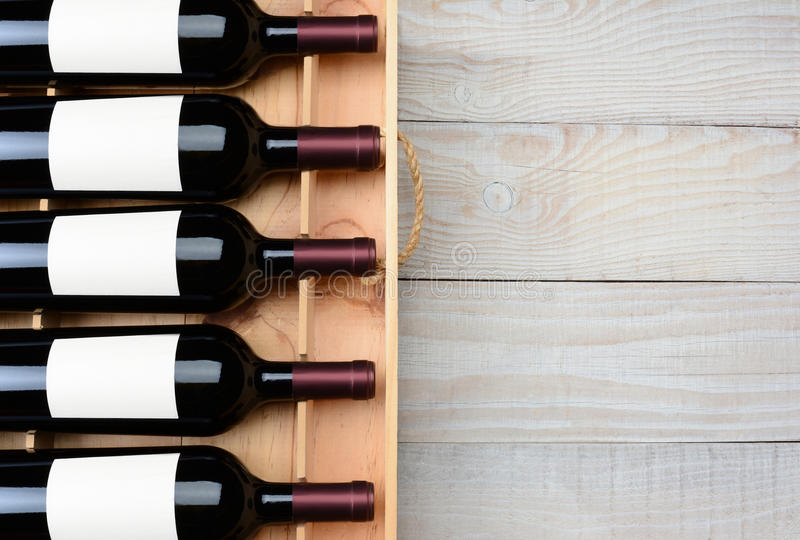 Wine Bottle Case Wood Table. High angle shot of a case of red wine bottles with blank labels on a rustic white wood table with copy space. Horizontal format royalty free stock photography