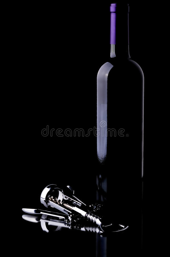 Wine Bottle and Chrome Corkscrew on Black royalty free stock image