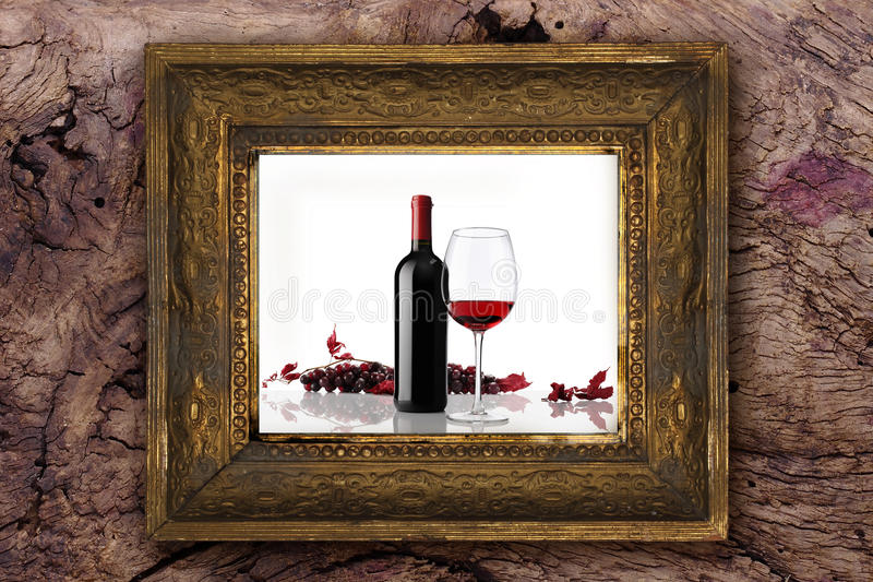 Wine bottle with glass and bunch of red grapes on old classic wooden frame carved by hand on wood background. Wine bottle with glass and bunch of red grapes on stock photography