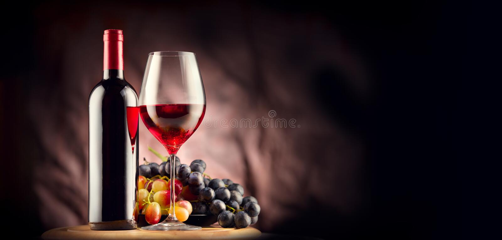 Wine. Bottle and glass of red wine with ripe grapes stock photo