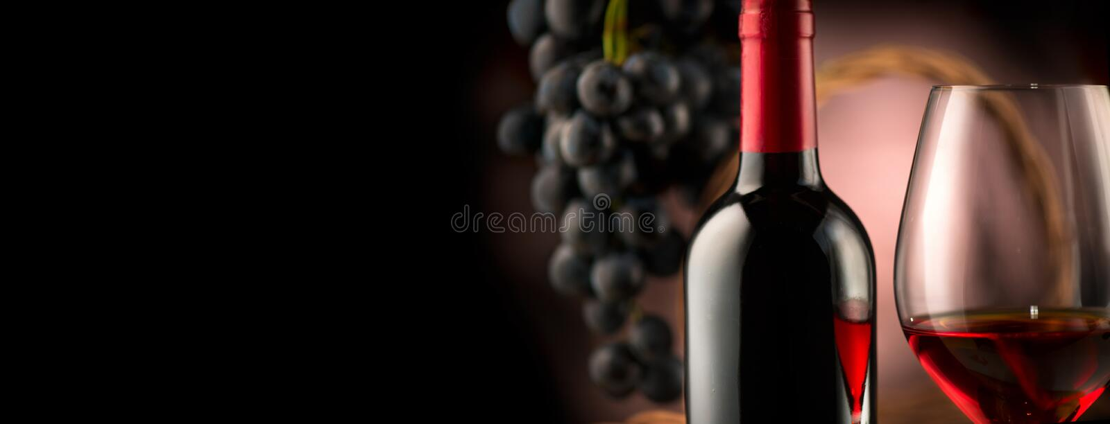 Wine. Bottle and glass of red wine with ripe grapes royalty free stock image
