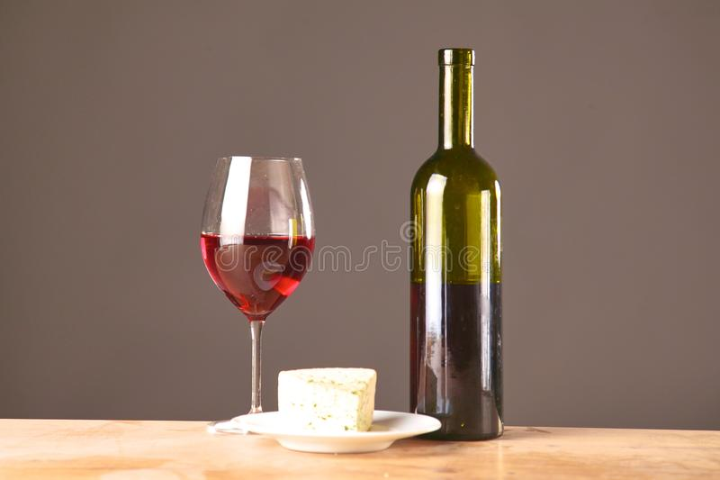 Wine bottle and wine glass on a glass table stock photography