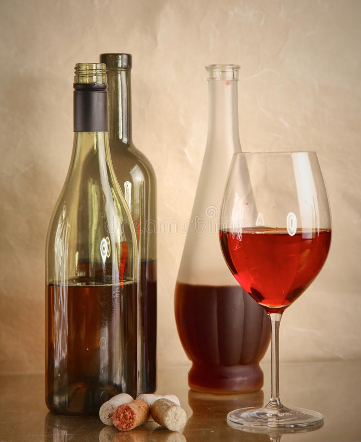 Wine bottle and wine glass on a glass table stock photos
