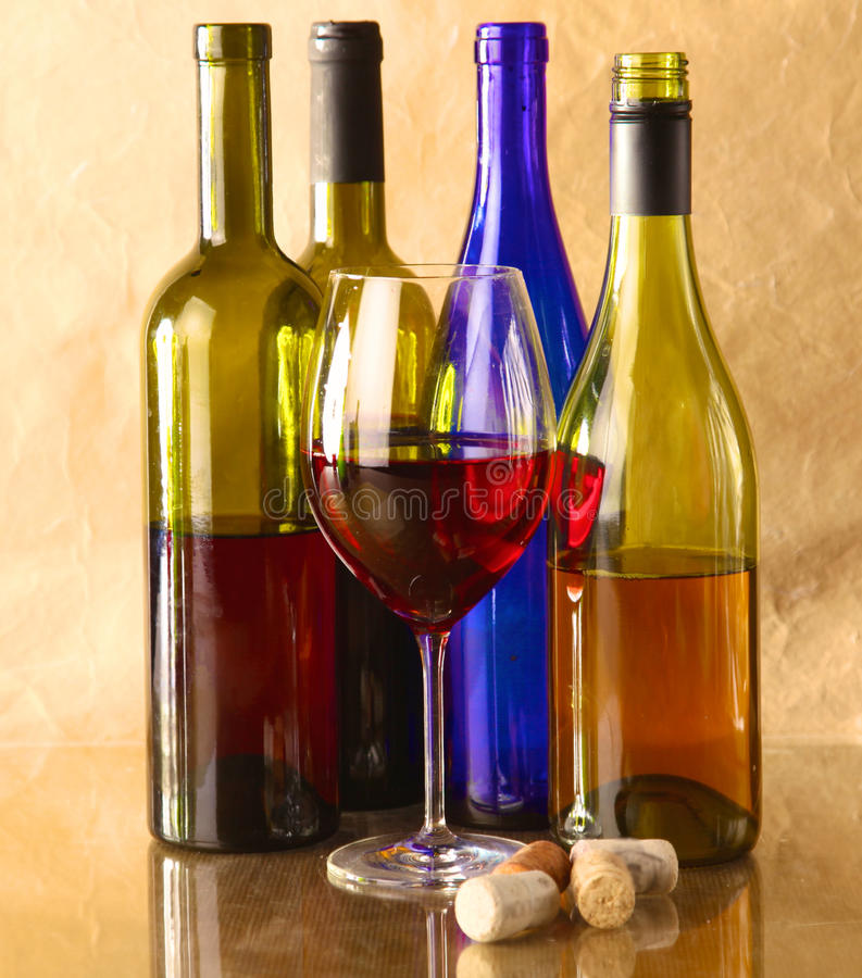 Wine bottle and glass on a table. Wine bottle and wine glass on a glass table royalty free stock images