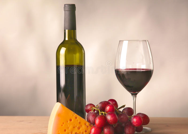 Wine bottle and glass on a table. Wine bottle and wine glass on a glass table stock image