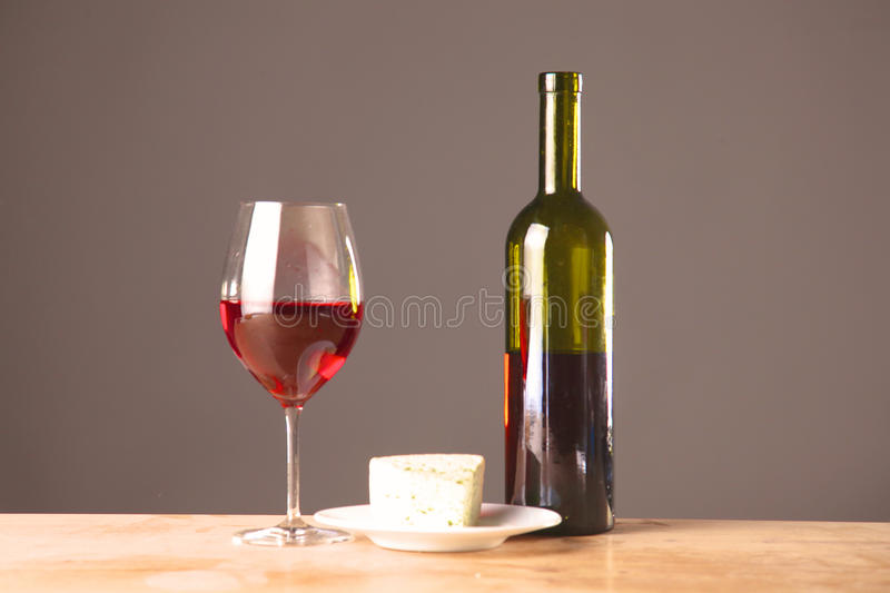 Wine bottle and glass on a table. Wine bottle and wine glass on a glass table royalty free stock image