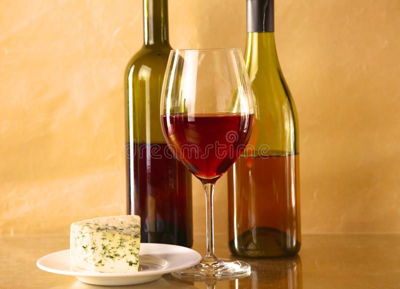 Wine bottle and glass on a table. Wine bottle and wine glass on a glass table stock photography