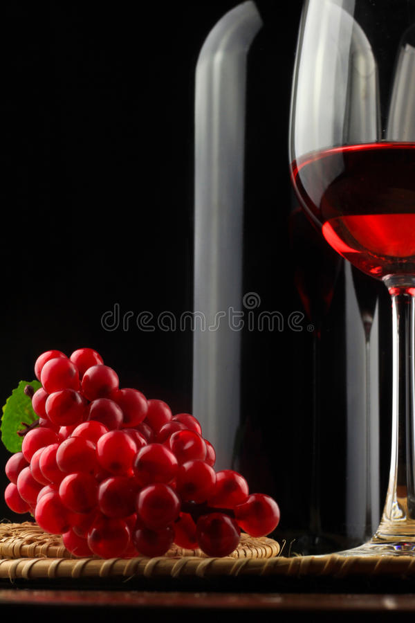 Wine bottle with a glass of wine on the trays royalty free stock photo