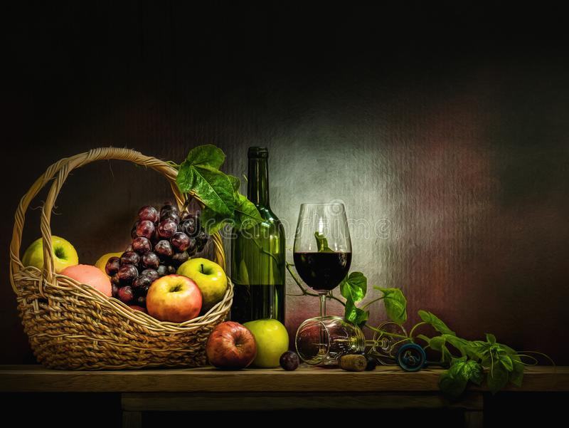 Wine bottle with glasses and basket of red grapes and apple on wooden table and background. Still life photography art of wine bottle with glasses and basket of royalty free stock photo