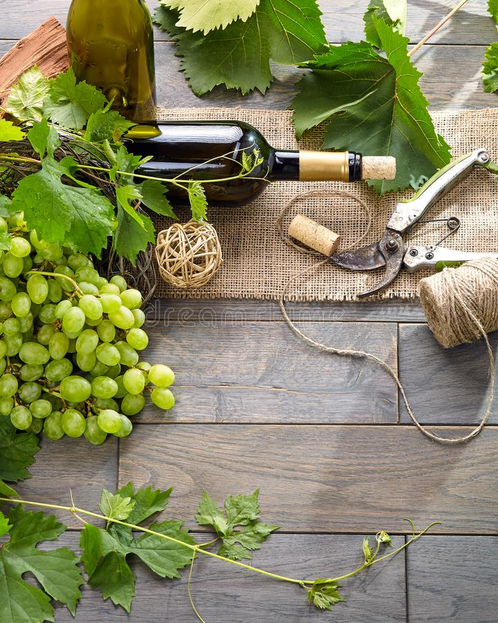 Wine bottle and grapes on wooden table. Top view with space for stock photos