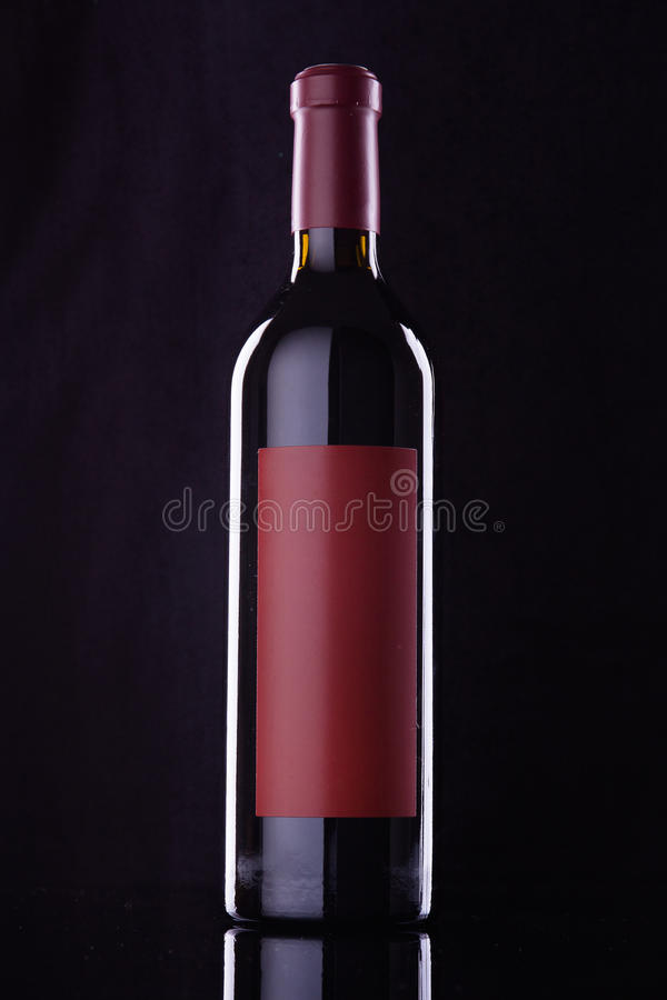 Wine bottle. With red lable on black stock photography