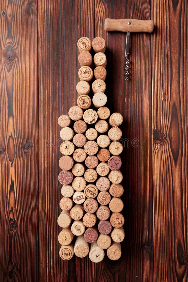 Wine bottle shaped corks and corkscrew over rustic wooden table background and burlap. Top view with copy space - image stock image