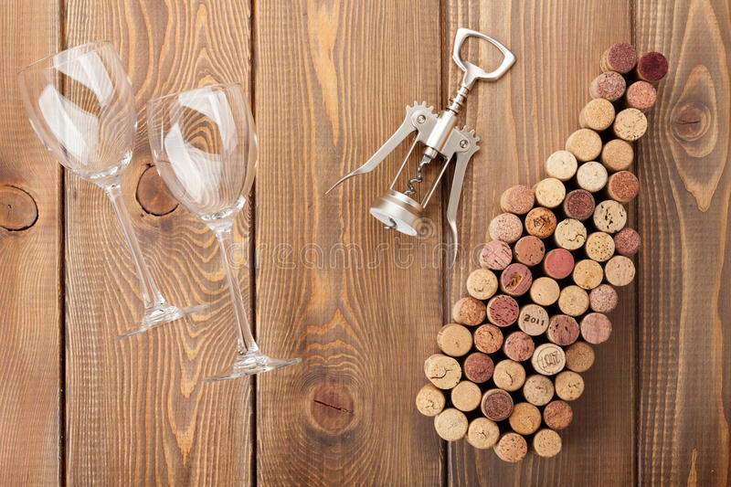 Wine bottle shaped corks, glasses and corkscrew. Over rustic wooden table background. View from above royalty free stock images