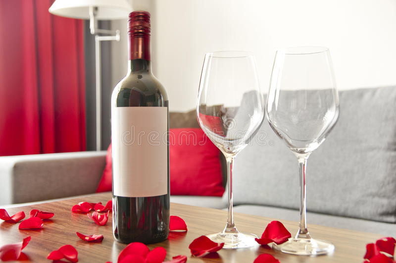 Wine bottle, two glasses and rose petals on a table - romantic a. Fternoon at home stock photo