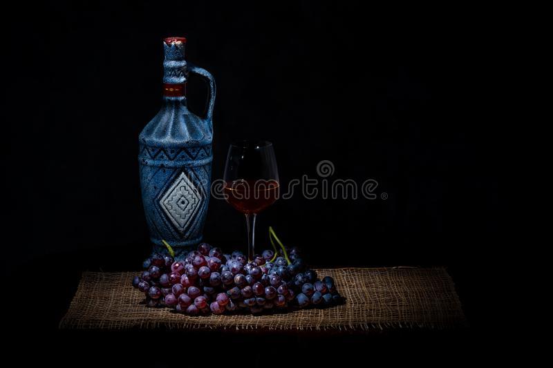 Wine bottle, wine glass and a bunch of grapes. Isolated on dark background using light painting technique royalty free stock images