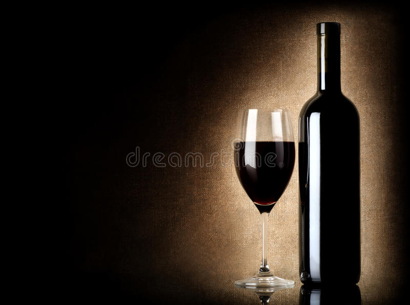 Wine bottle and wineglass on a old background stock image