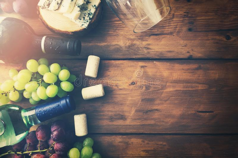 Wine bottles grapes and cheese on wooden background. top view royalty free stock photo