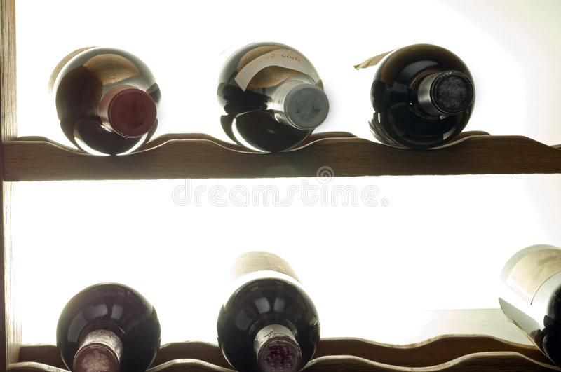 Wine bottles in rack. Backlighted backlit close shot of six assorted wine bottles with labels and cork wraps in a floor wine rack against a white background with royalty free stock images