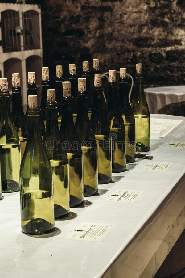 Wine bottles stand in a row on the table stock image