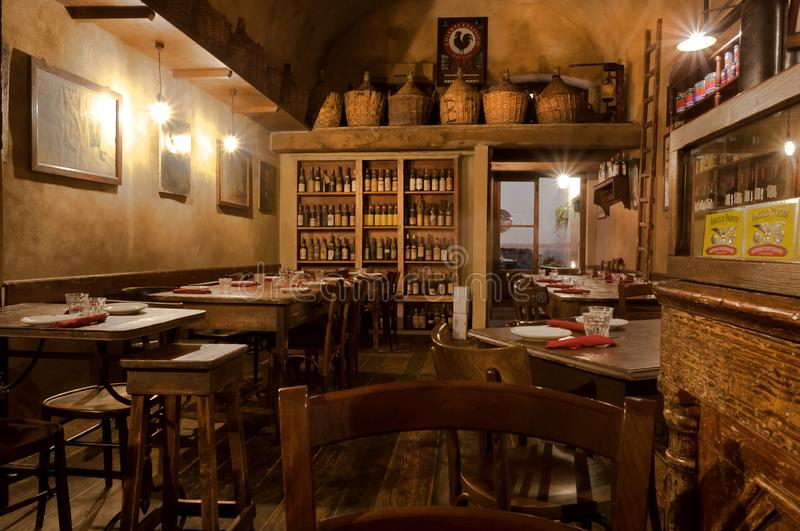 Wine bottles and wooden vintage furniture inside traditional italian restaurant royalty free stock image