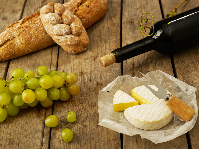 Wine, bread, cheese and grapes stock photos