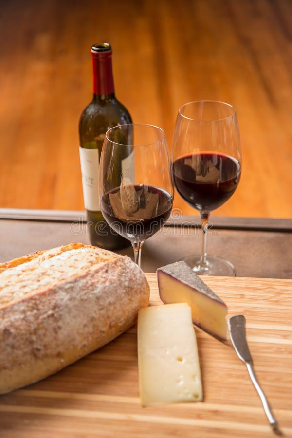 Wine, bread and cheese in vertical format. Red wine, loaf of bread and a variety of cheeses in vertical format royalty free stock photo