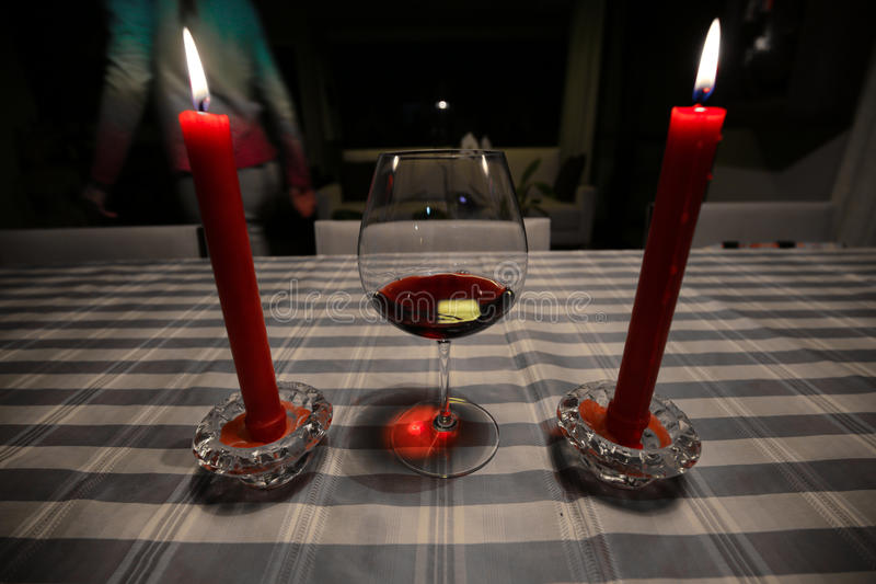Wine and candles. Attractive woman leaves table with a half full wine glass and two candles stock image
